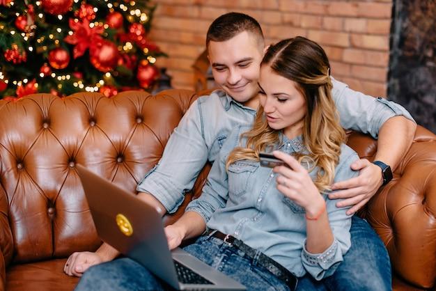 Le mari et la femme paient en ligne les achats par carte de crédit à domicile