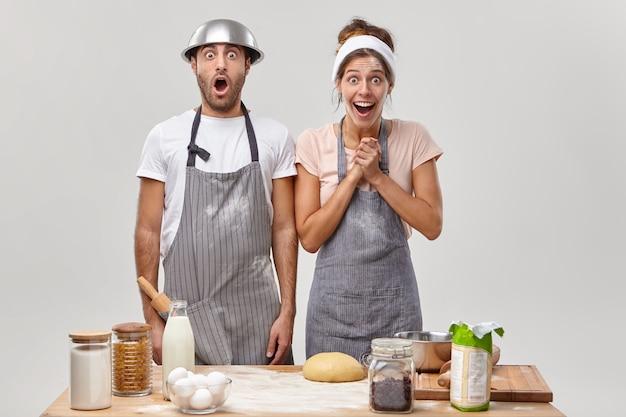 Mari et femme posent dans la cuisine en préparant un délicieux dîner