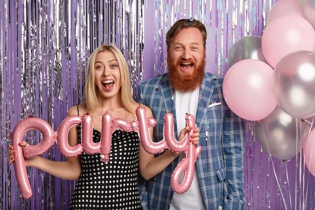 Un mari et une femme positifs organisent une fête avec des amis, tiennent des ballons à air, portent une tenue de fête, se tiennent ensemble contre le mur du studio décoré de violet