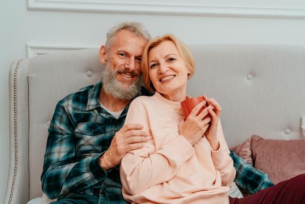 Le mari et la femme prennent le petit déjeuner avec du café sur le lit à la maison