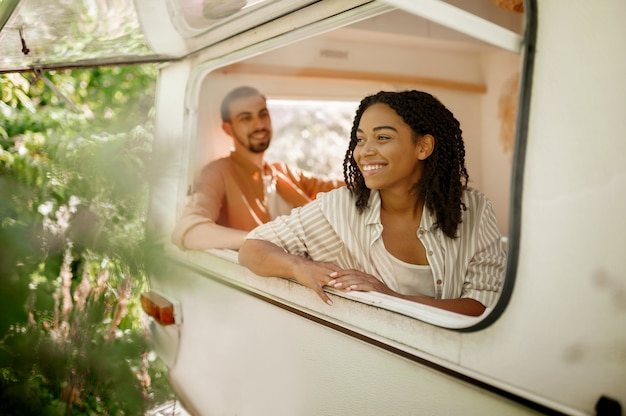 Mari et femme regarde par la fenêtre du camping-car, campant dans une remorque. homme et femme voyagent en van, vacances romantiques en camping-car, loisirs campeurs en camping-car