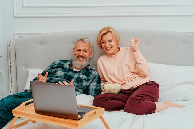 Mari et femme regardent un film sur le lit et mangent du pop-corn
