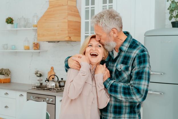 Mari et femme à la retraite s'embrassent à la maison