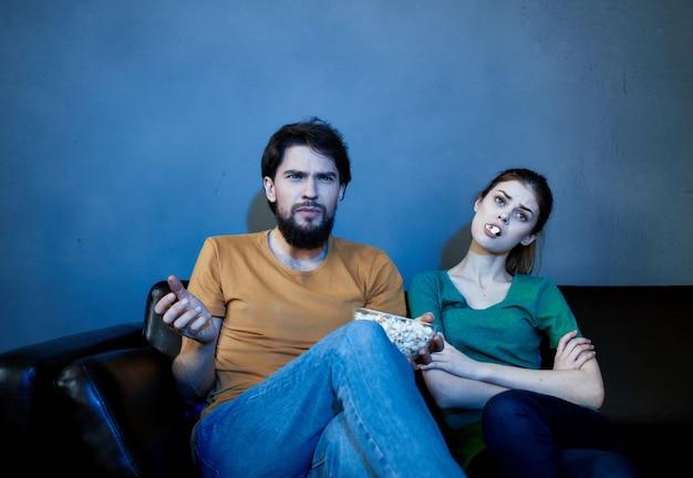 Le mari et la femme sont assis à la maison le soir sur le canapé en train de regarder la télévision se reposer