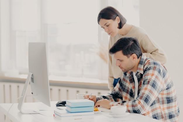 Le mari et la femme travaillent ensemble sur des rapports, vérifient les informations, s'assoient devant un ordinateur, boivent du café, portent des vêtements décontractés, collaborent pour travailler en équipe. concept de travail familial et à distance