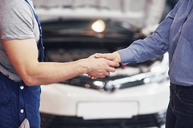 Mari mécanicien automobile et femme cliente concluent un accord sur la réparation de la voiture