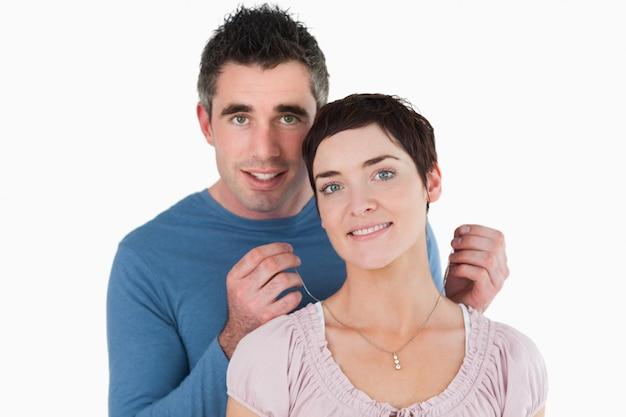 Mari offrant un collier à sa femme sur un fond blanc