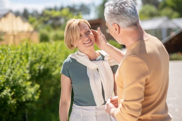 Mari romantique amoureux aux cheveux gris caressant le visage de sa jolie femme souriante et satisfaite d'âge moyen pendant la promenade matinale