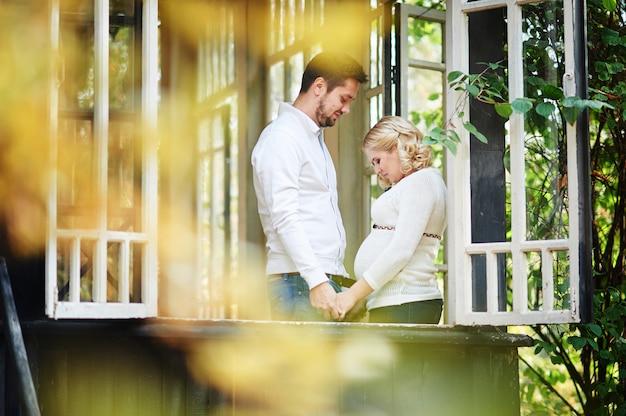 Mari avec sa femme enceinte sur le porche de la maison
