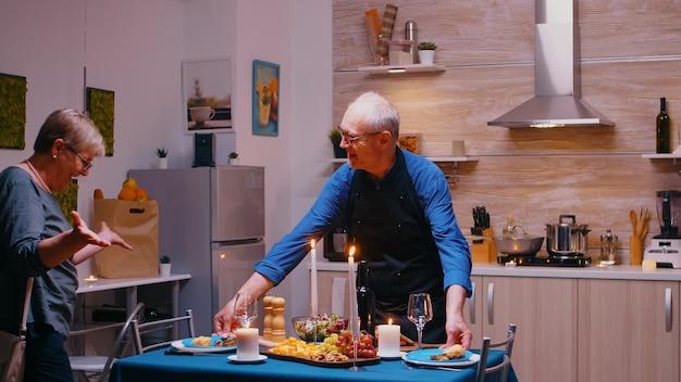 Mari senior surprenant sa femme avec un dîner romantique. vieux couple de personnes âgées parlant, assis à table dans la cuisine, savourant le repas, célébrant leur anniversaire avec des aliments sains.