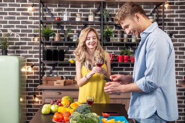 Mari serviable. heureuse épouse regardant son mari serviable préparer le dîner pour leur soirée romantique