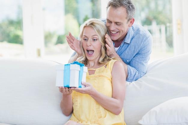 Mari surprenant avec un cadeau dans le salon