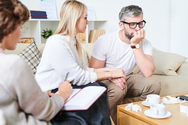 Un mari triste soutenu par une femme visitant un psychiatre