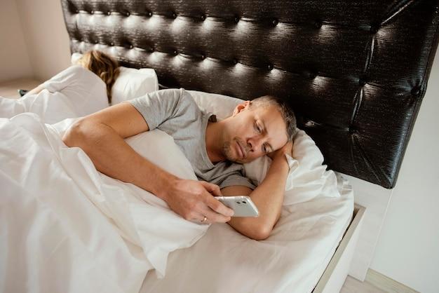Mari utilisant un mobile pendant que sa femme dort