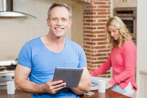 Mari utilisant une tablette pendant que sa femme déjeune dans la cuisine