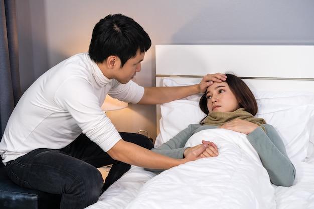 Mari visitant et prenant soin de sa femme malade pendant qu'elle est allongée sur le lit à la maison