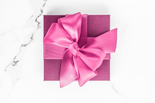 Mariage d'anniversaire et concept de marque girly coffret rose avec noeud en soie sur fond de marbre cadeau de douche de bébé fille et cadeau de mode glamour pour la conception d'art flatlay de vacances de marque de beauté de luxe