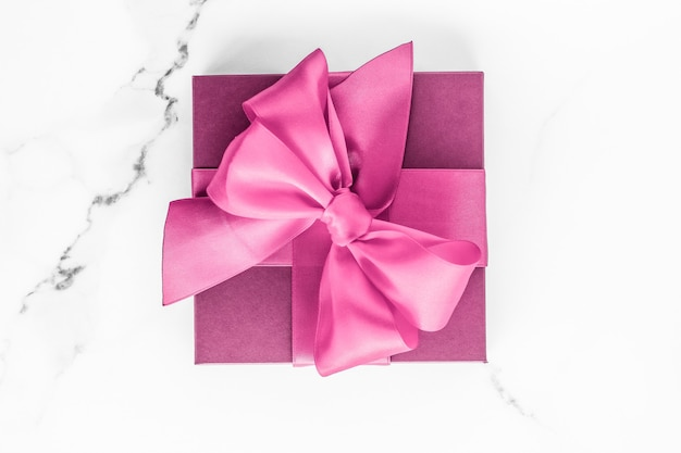 Mariage d'anniversaire et concept de marque girly coffret rose avec noeud en soie sur surface en marbre cadeau de douche de bébé fille et cadeau de mode glamour pour la conception d'art flatlay de vacances de marque de beauté de luxe
