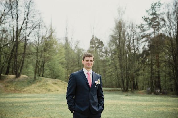 Mariage au printemps. le marié en costume bleu et cravate rose. portrait.