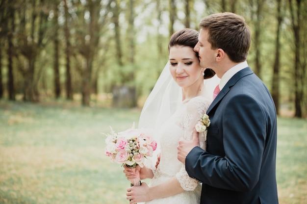 Mariage au printemps. le marié embrasse et embrasse la mariée. robe blanche. un bouquet rose.
