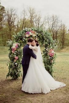 Mariage au printemps. le marié embrasse et embrasse la mariée. robe blanche.