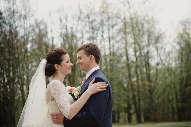 Mariage au printemps. le marié embrasse la mariée. robe blanche. un bouquet rose.