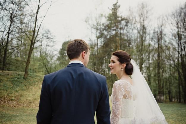Mariage au printemps. la mariée et le marié vont à la cérémonie par la main, se regardent.