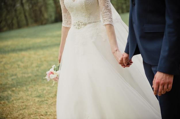 Mariage au printemps. la mariée et le marié vont à la cérémonie par la main.
