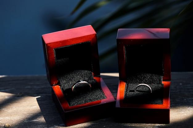 Mariage bagues en diamant dans une boîte brillante rouge sur le vieux fond en bois avec tache