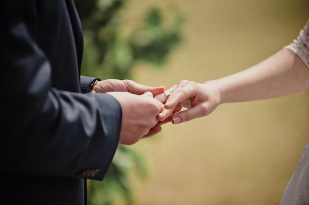 Mariage classique au printemps. cérémonie et un arc avec des fleurs fraîches. la mariée et le marié échangent des anneaux.