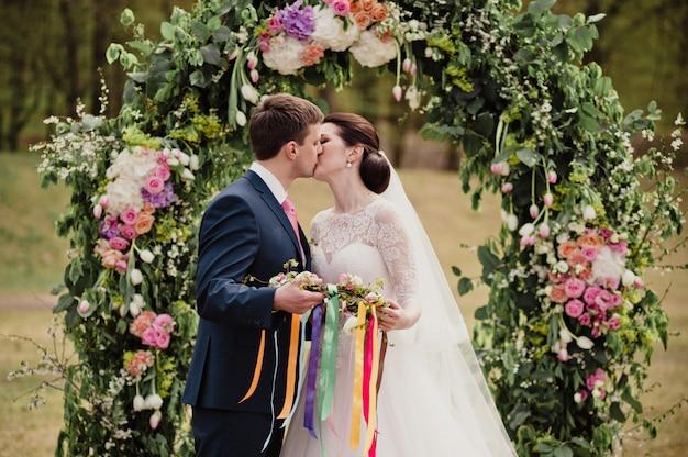 Mariage classique au printemps. cérémonie et un arc avec des fleurs fraîches. rite avec des rubans. création d'une amulette familiale. tradition. la mariée et le marié s'embrassent.