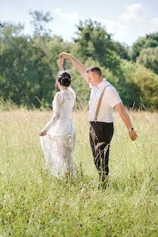 Mariage d'un jeune beau couple dans un style vintage. jeunes mariés en promenade dans le parc