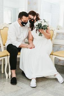 Mariage pendant l'épidémie de coronavirus. mariée et marié dans des masques médicaux de protection. mariés et pandémie de covid-19.
