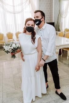 Mariage pendant l'épidémie de coronavirus. mariée et marié dans des masques médicaux de protection.