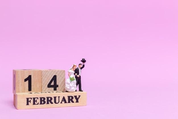 Mariage de personnes miniatures, couple de jeunes mariés sur fond rose,