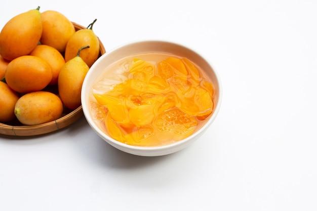 Marian prune fruits au sirop avec de la glace dans un bol blanc sur une surface blanche