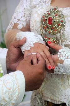 Le marié attache la bague de mariage à l'annulaire de la mariée