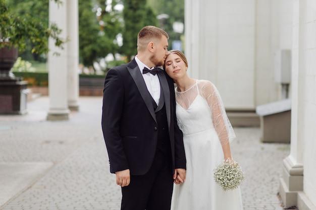 Un marié barbu et élégant en costume et une belle mariée blonde en robe blanche avec un bouquet dans les mains se tiennent debout et s'embrassent dans la nature dans la forêt de pins.