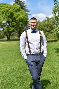 Marié en chemise dans un parc d'été