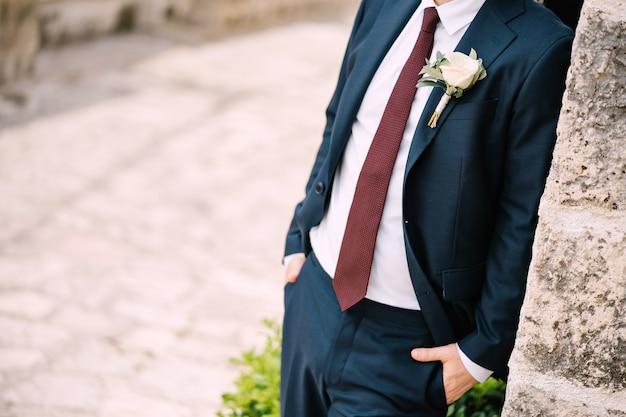 Le marié en costume avec une cravate rouge et une boutonnière avec une rose blanche dans la rue de la vieille ville