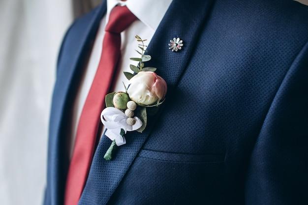 Le marié en costume et cravate rouge