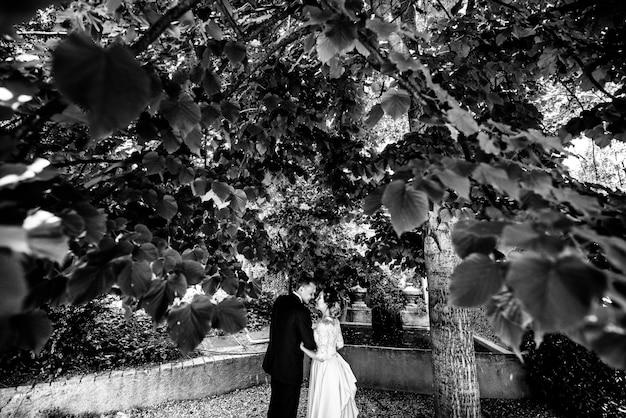 Le marié en costume et la mariée en robe de mariée se promènent dans le parc