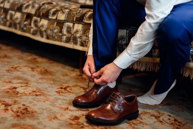 Marié en costume noue les lacets sur les chaussures marron