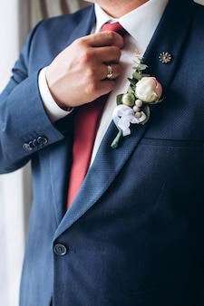 Le marié en costume redresse sa cravate