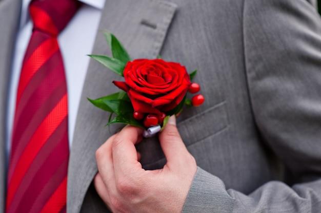 Marié en cravate rouge avec rose sur sa veste