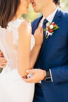 Le marié dans un costume bleu embrasse la mariée dans une robe en dentelle blanche