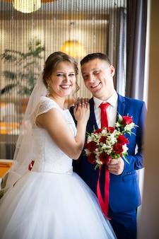 Le marié dans un costume bleu et la mariée dans une robe de mariée les jeunes mariés, embrassant, posent ensemble au café