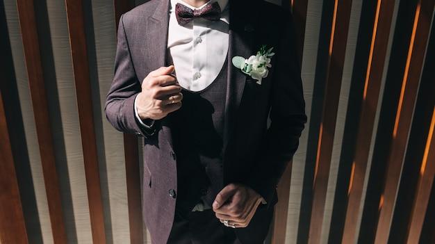 Le marié dans un costume de mariage marron, un smoking dans une chemise blanche et une boutonnière