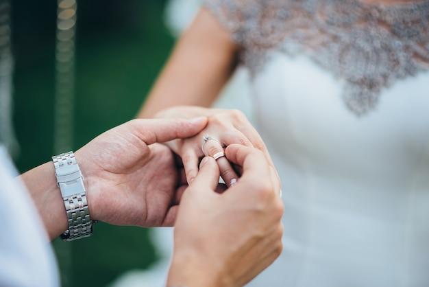 Le marié dans une montre et un costume met la bague de mariage au doigt de la mariée
