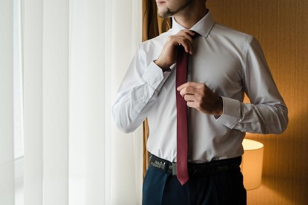 Marié dans une veste bleue les frais de palefrenier l'homme redresse sa veste